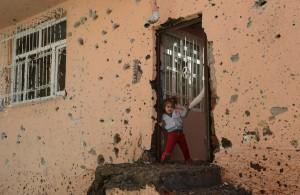Δεκέμβρης στη Σουρ. Η μικρή κούρδισσα επιχειρεί να βγει από το σπίτι και το χέρι της μάνας την τραβά πίσω, στην όποια «ασφάλεια» του σπιτιού.