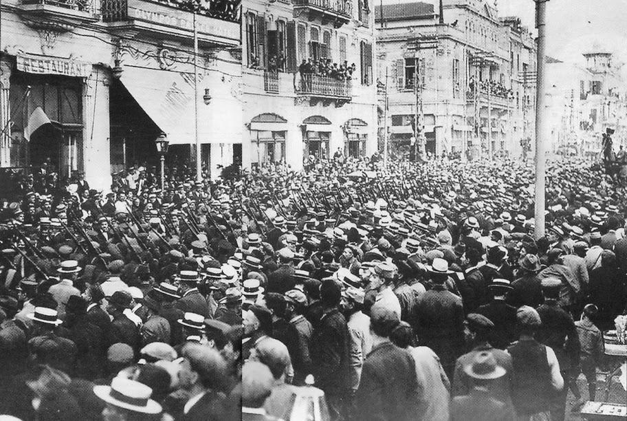 Οι δυνάμεις της «Εθνικής Άμυνας» παρελαύνουν στη Θεσσαλονίκη.  Ήταν το προανάκρουσμα της συμμετοχής της χώρας στο Α΄ Παγκόσμιο Πόλεμο, στο πλευρό της Αντάντ.